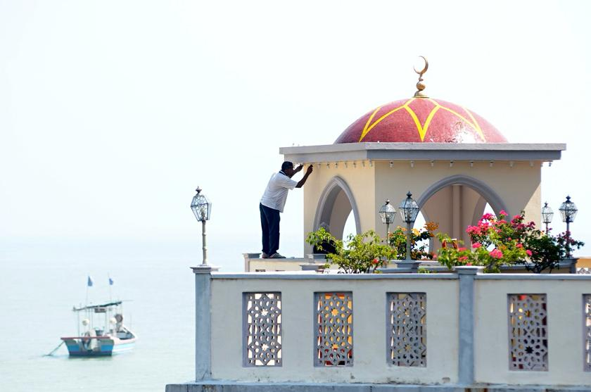 A mosque helper carries out some maintenance work on the Tanjung Bungah floating mosque in George Town February 12, 2014. — Picture by K.E. Ooi