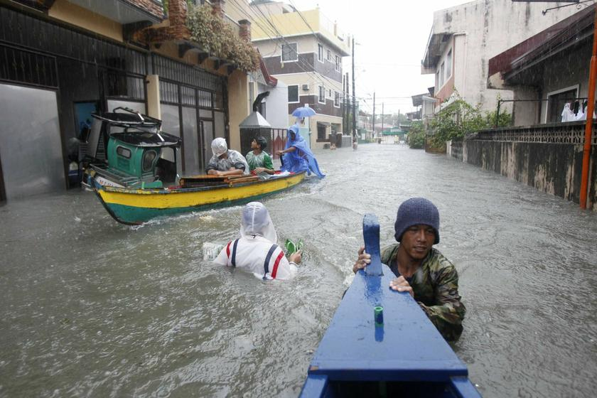 Residents wade in floodwaters brought by monsoon rain, intensified by tropical storm Trami, in Kawit town of Cavite city, south of Manila August 19, 2013