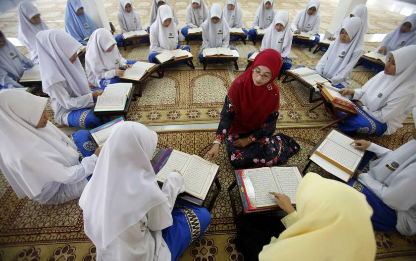 Muslim schoolgirls sit in a circle around their religious teacher as they recite verses from the Quran on the occasion of 'Nuzul Quran' in Putrajaya on July 26, 2013. — Reuters pic