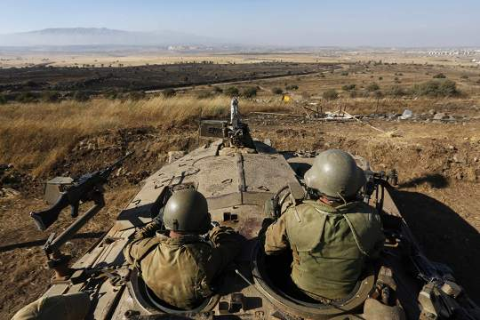 Israeli soldiers sit atop a tank as they watch the border with Syria near the Quneitra border crossing between Israel and Syria, on the Israeli-occupied Golan Heights July 3, 2013. — Reuters pic