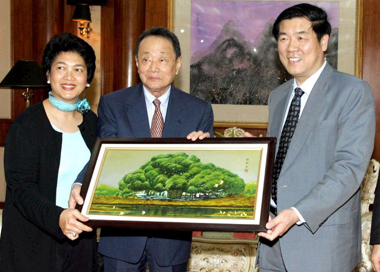 Malaysia's richest man Robert Kuok (centre) receives a souvenir from a Chinese official (right) during his visit to Fuzhou, in southeastern China's Fujian province, 18 April 2005, as president of the Kuok clan in Malaysia. — AFP pic