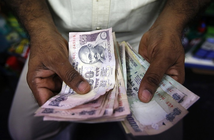 A private money trader counts Indian rupee notes at a shop in Mumbai, in this August 1, 2013 file photo. Malaysian money changers have frozen Indian currency trading after India announced the scrapping of two bills. — Reuters pic