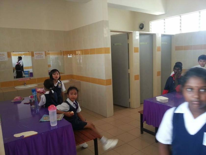 Students are seen eating their recess meals inside the toilet.