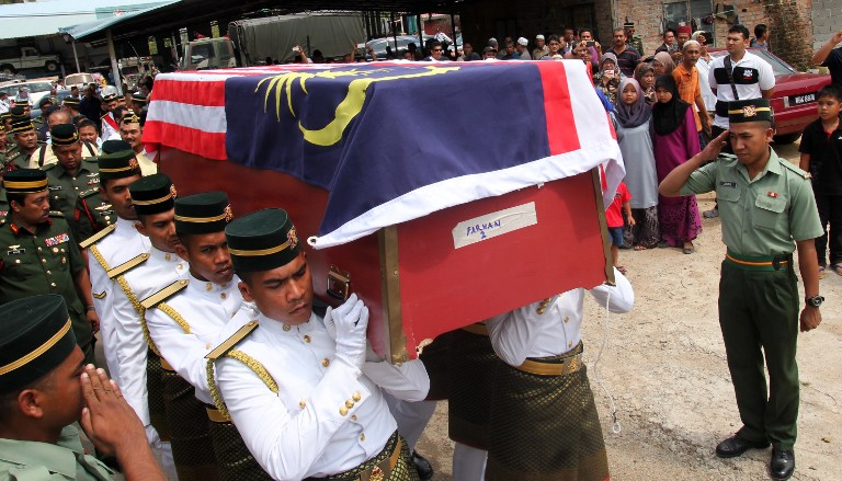 Malaysian soldiers carry a coffin containing the remains of Ahmad Farhan Roslan, who was killed in an accident while traveling to transport food during a stand-off with Sulu gunmen near Tanduo  on March 13, 2013. – AFP pic