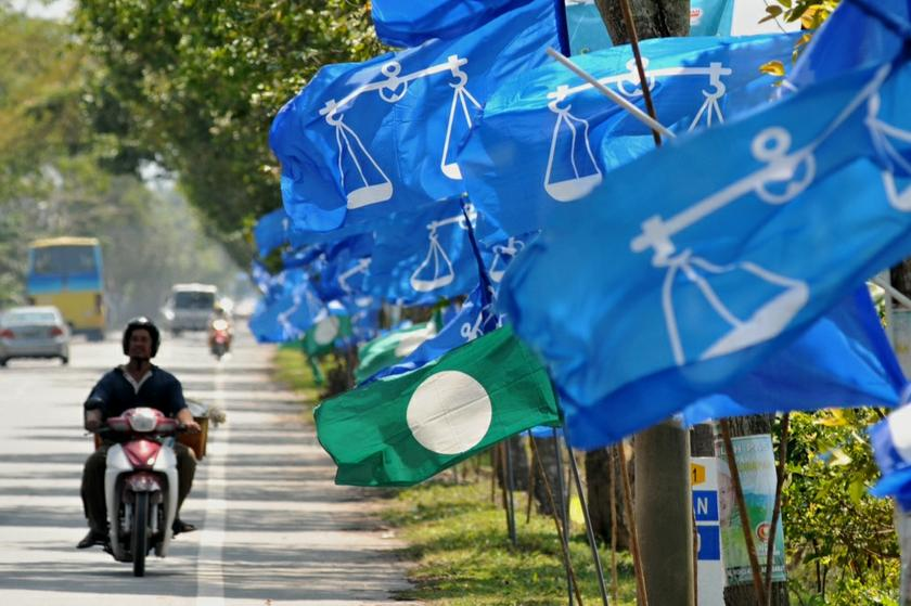 A motorist passes a row of Barisan Nasional and PAS flags during the run up to the Sungai Limau by-election at Sungai Kering in Sungai Limau, Kedah, October 31, 2013. — Picture by KE Ooi