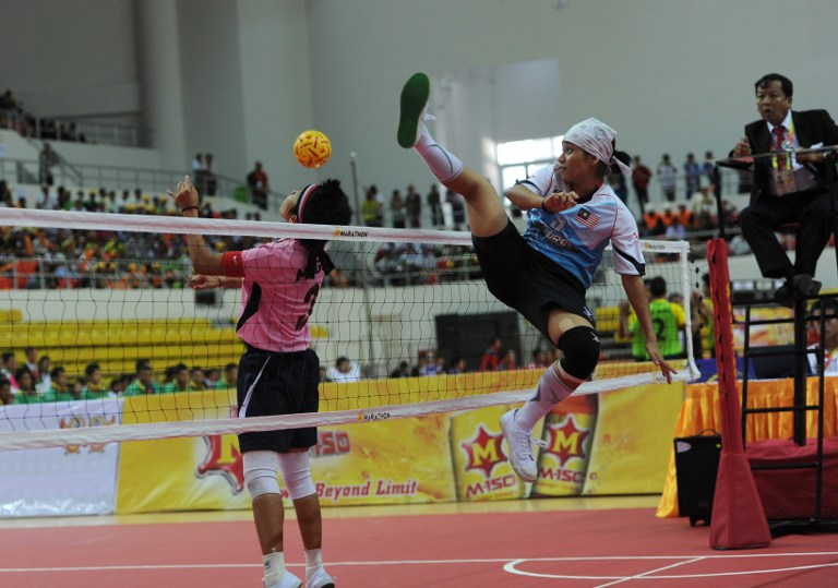 Nurrashidah Abdul Rashid (right) from Malaysia attempts a block as Mega Citra from Indonesia heads during the Sepaktakraw women's event during the 27th Southeast Asian Games in Naypyidaw on December 12, 2013. — AFP pic