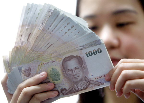 File photo of a bank cashier counting Thai baht notes in a bank in Bangkok. — AFP pic