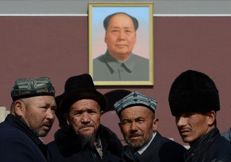 File photo of Uighurs from Xinjiang Province posing for photos in front of a portrait of Mao Zedong before the opening session of the Chinese People's Political Consultative Conference (CPPCC) at the Great Hall of the People in Beijing on March 3, 2013.