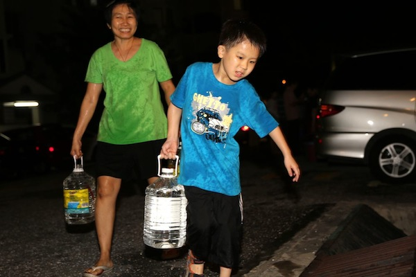 A boy helps his mother carry water home, as supplied by a tanker, following a water cut in Puchong, August 31, 2013. — Picture by Choo Choy May